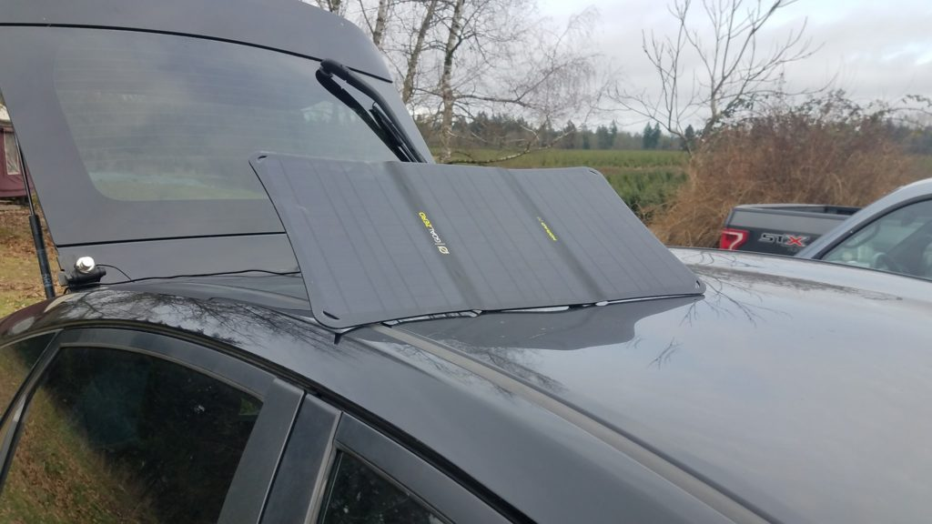 Folding solar panel placed on top of the car roof with cable running to hatch back.