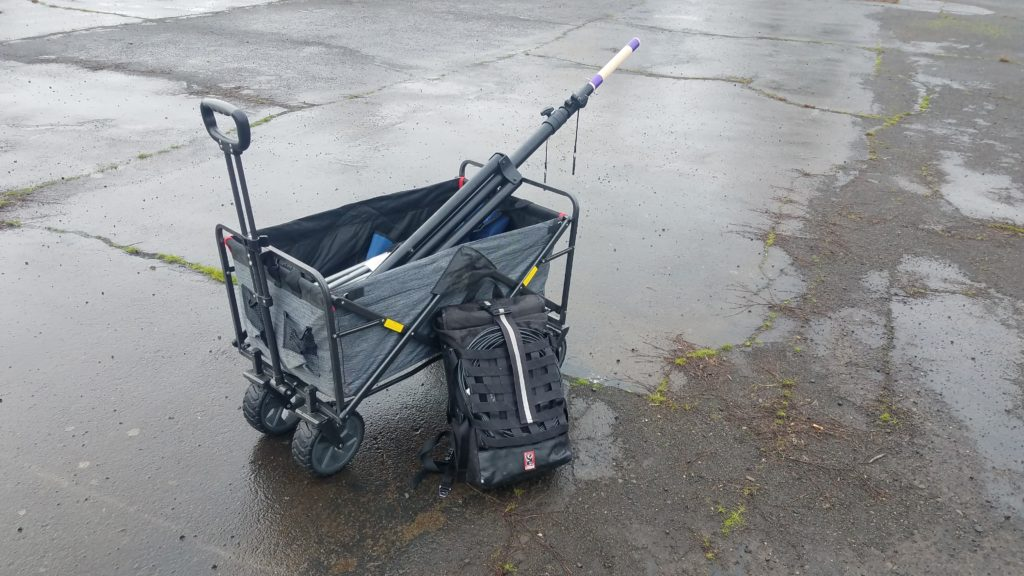 Cloth-sided wagon containing various equipment and a backpack leaning against the side.