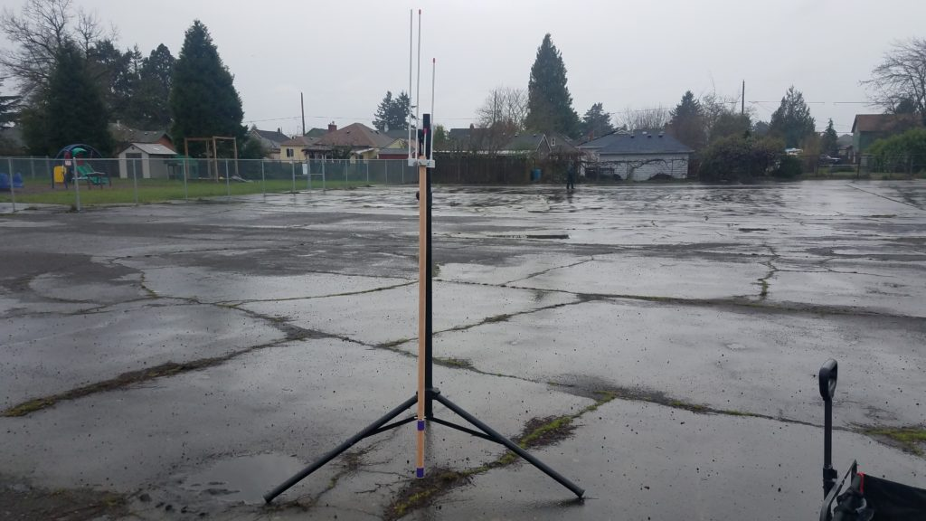 J-pole mounted to a wooden closet rod resting against a speaker stand. The split 2m element is affixed for transport.