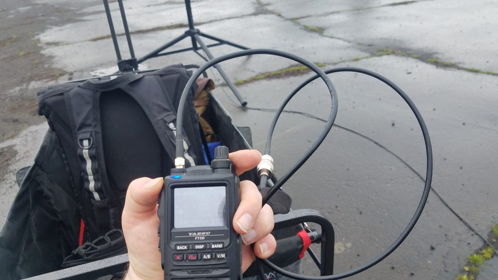 Yaesu FT3DR connected to the feedline with the wagon and antenna stand in the background.