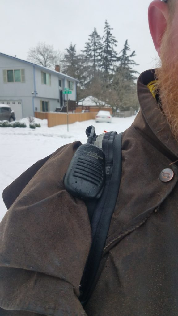 Yaesu speaker microphone clipped to a backpack strap.