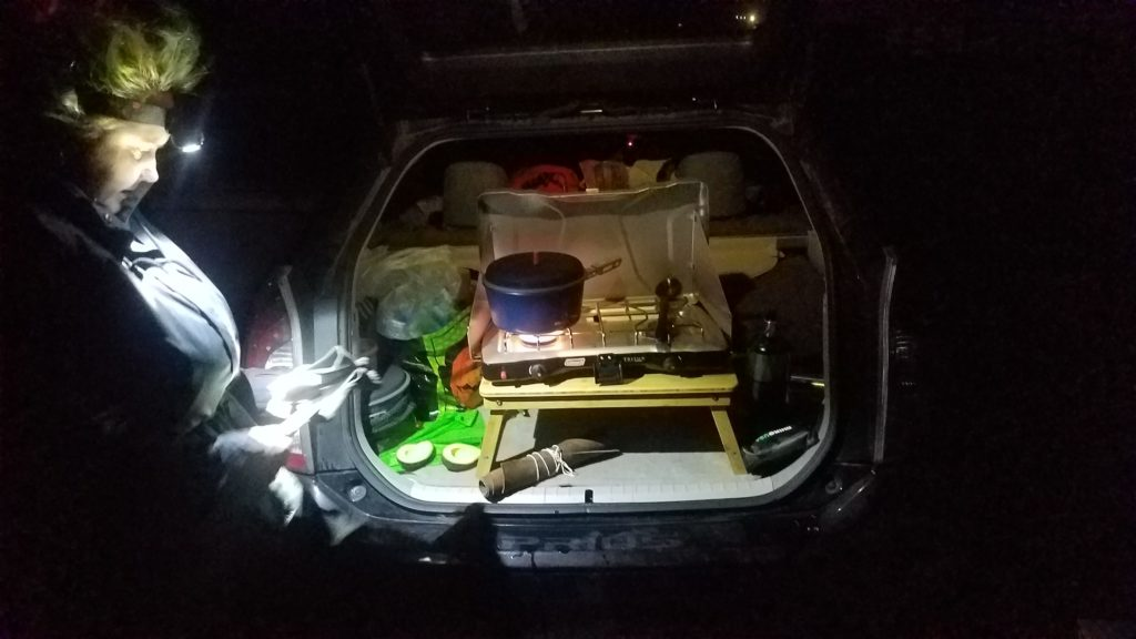 A burning camp stove sitting in the back of a vehicle with its hatch back open in the dark. The stove has a pot on one burner with an avacado and knife roll near it. A woman stands to the left with a head lamp helping prepare food.