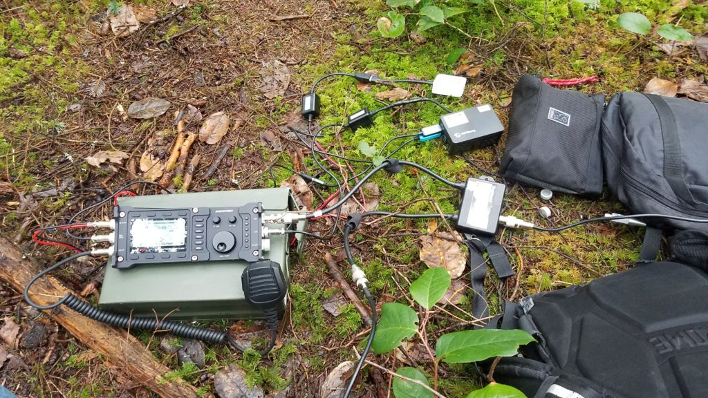 A radio sitting on top of an ammo can attached by cable to a duplexer and, Raspberry Pi 4 in a case. A small travel router is also attached by power cable to the ammo can. A number of small bags and a backpack are visible in and partially in frame. The ground is a forest floor with branches, sticks, lichens, and leaves on the ground.