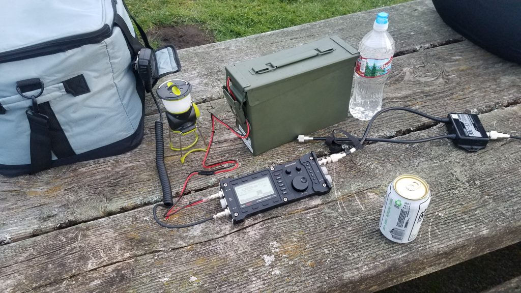 A soft-sided cooler, LED lantern, water bottle, beverage in a can, and a radio attached to an ammo can by a power cable and a duplexer sitting on top of a wooden park bench.
