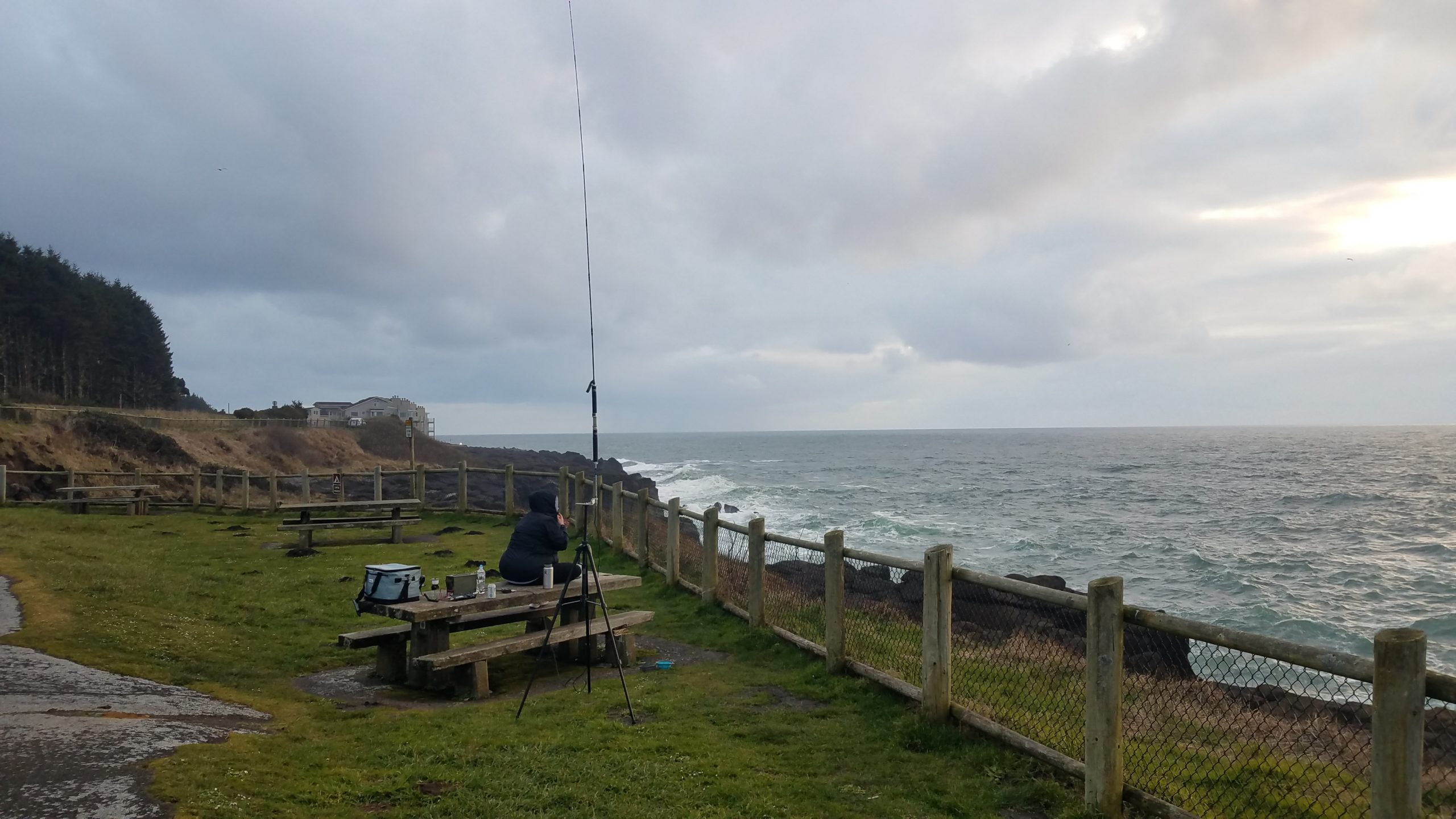 View of a grassy area surrounded by a wood and metal mesh fence, and trees with a wooden table, fence, and ocean in the background. The sky is cloudy and ocean waves crash against rocks. A woman sits on a wooden table with a cooler, drinks, and radio equipment staring at the ocean with an antenna near the table.