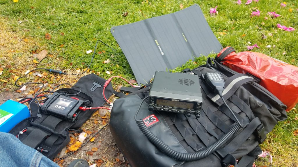 A radio sitting on top of a backpack connected to a solar charger, solar panel, and battery.