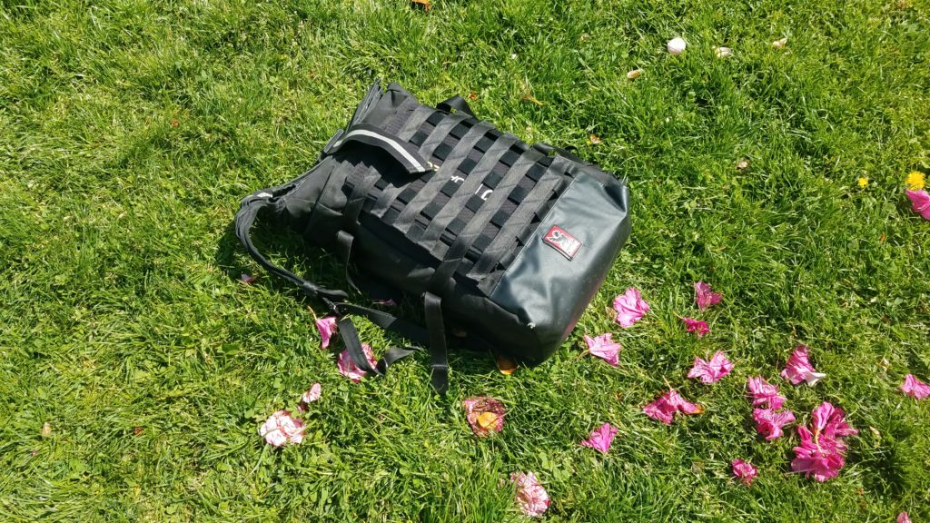 Closed backpack on the groud with a folded solar panel in the attached cargo net.