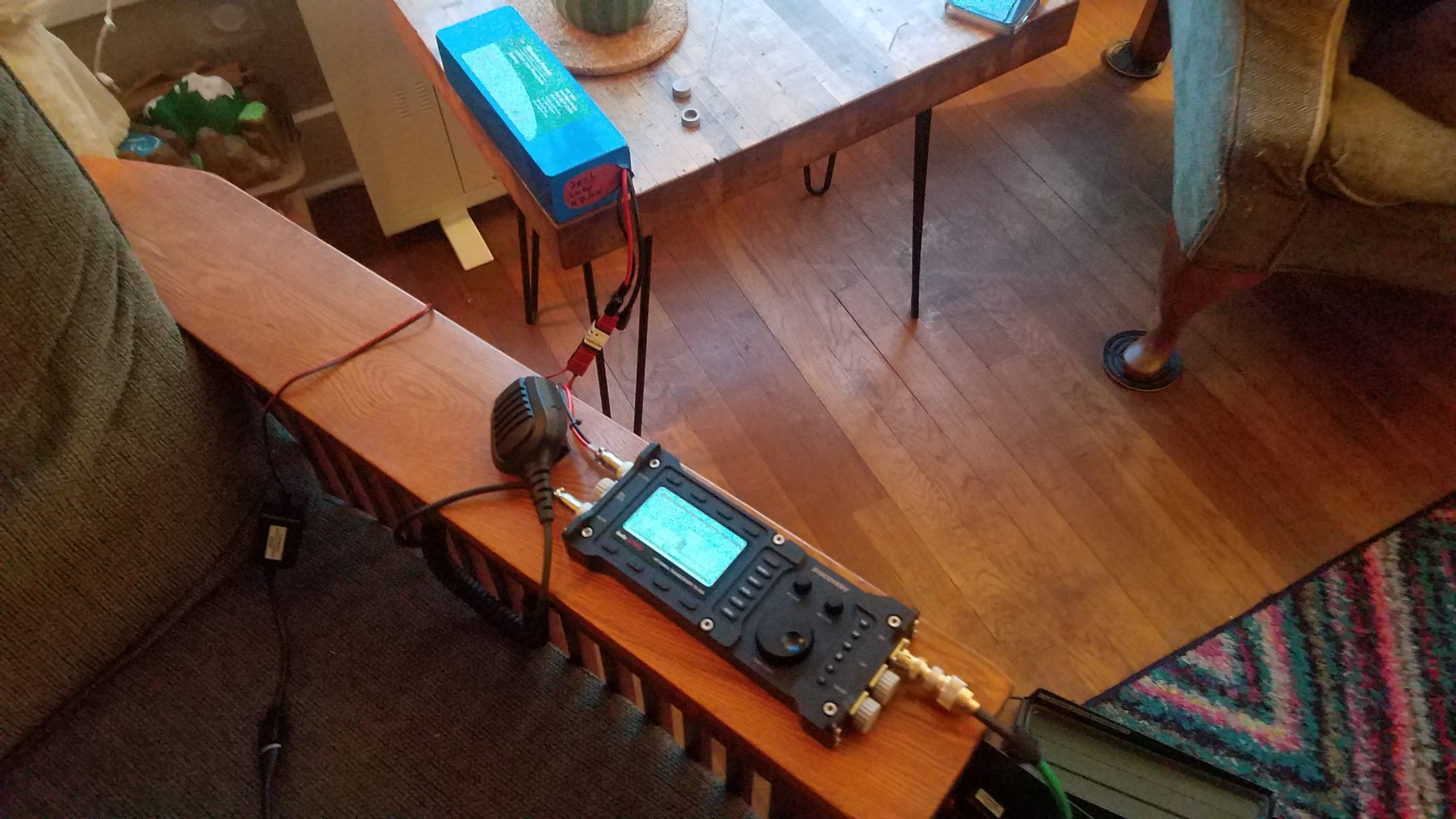 Zoomed out view of a radio sitting on a chair arm connected to a 12v battery and a 12v USB phone charger.