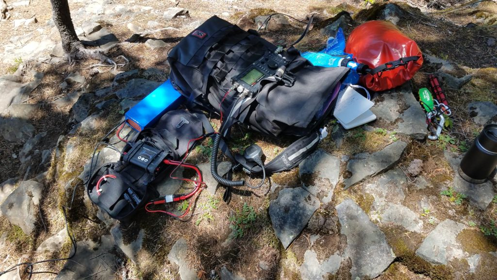 A battery, charge controller, and radio on top of a backpack as well as a coffee cup, arborist's thorwing weight, water bags, a notebook, and a red waterproof bag.