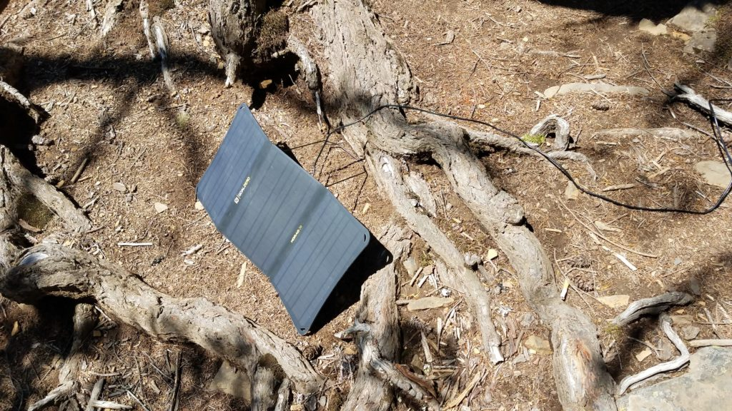 A Goal Zero Nomad 20 solar panel set up on the ground in the sun.