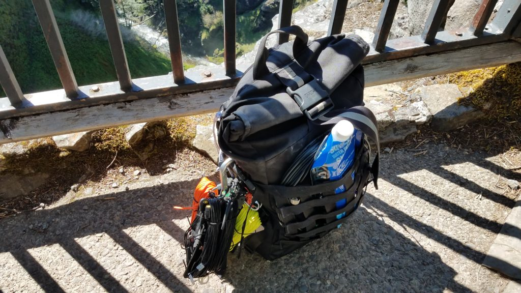 Black backpack with an antenna and paracord attached to the outside of the bag along with feed line and water bags attached sitting on pavement against guard rails with a waterfall in the background.