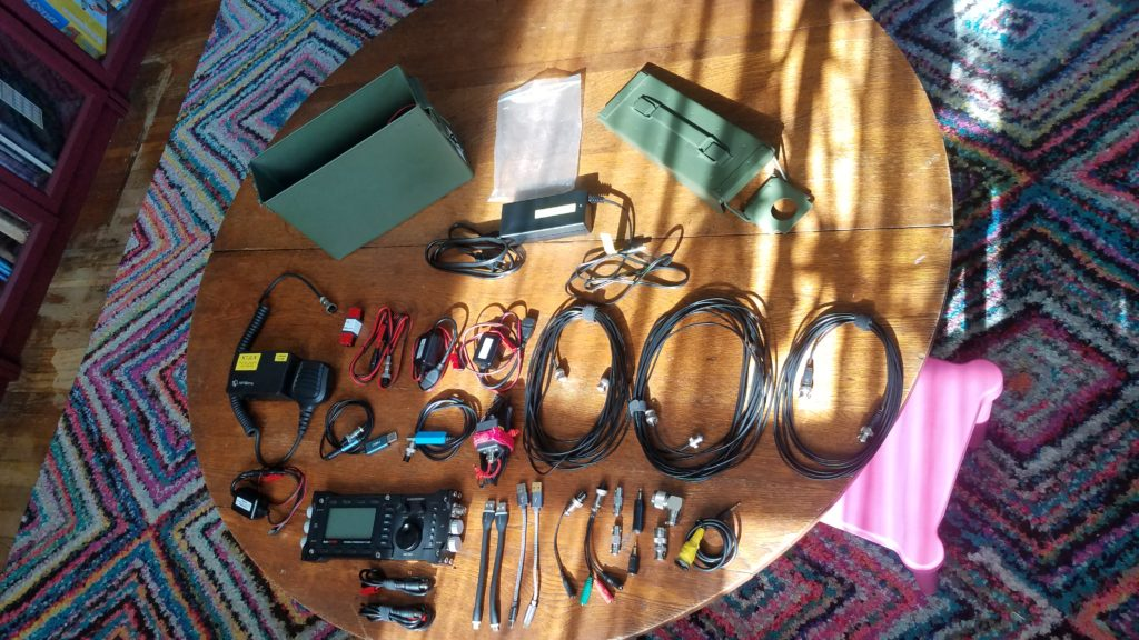 Ammo can and its lid as well as several cables and devices are laid out on a wooden table.
