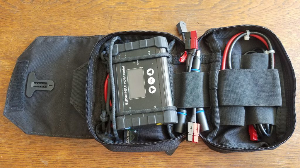 An opened cloth pouch open revealing devices and cables secured to the inside with paracord and elastic bands.