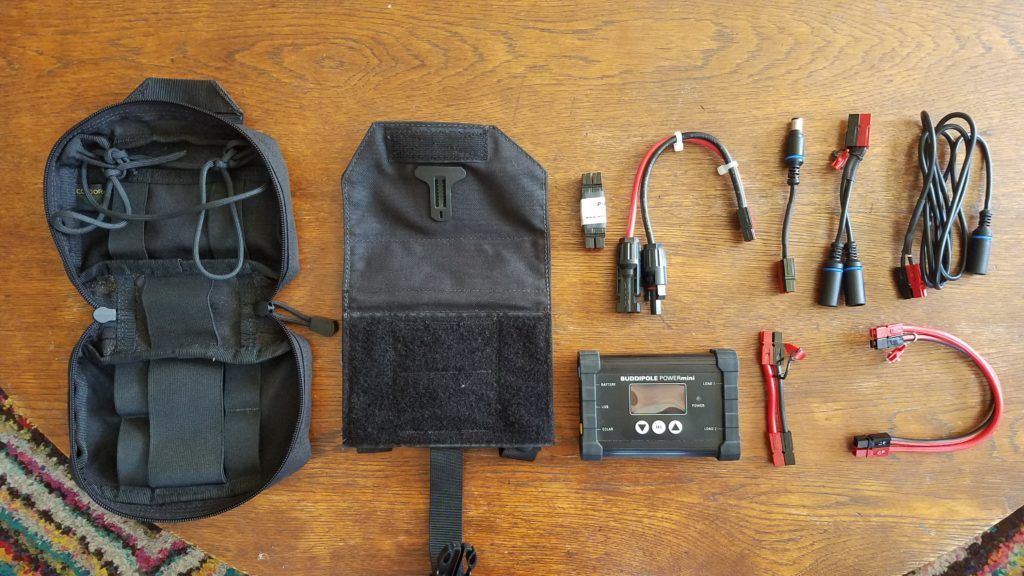 An empty cloth pouch, a velcro-backed sleeve, various cables and devices laid out on a wooden table.