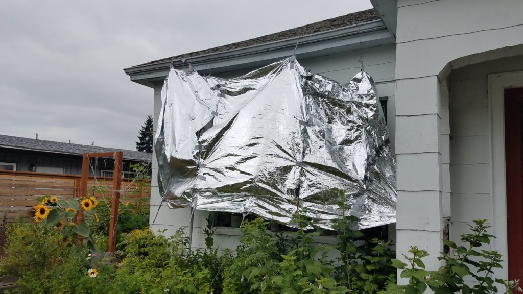View of the outside of a house with a mylar blanket suspended in front of a large window supported by paracord. There are lots of plants.