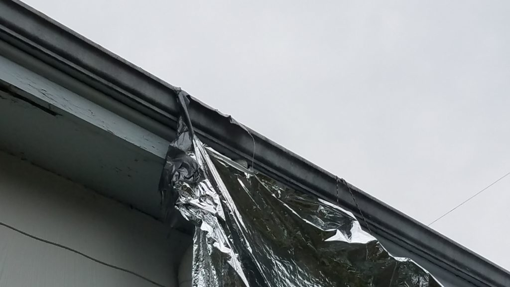 One corner of a mylar blanket duct taped to the inside of a rain gutter. The tape is coming off the gutter in spots and the blanket is precariously attached.