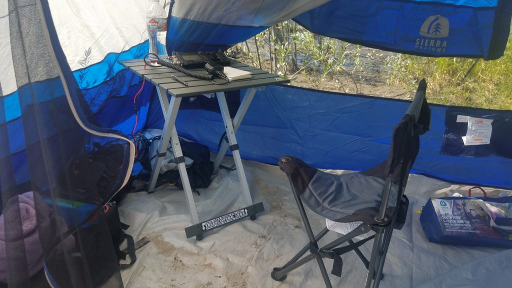 Interior view of a tent front the door showing a small folding table, three-legged folding camp chair and equipment resting against the walls of the tent. Through the mesh you can see the river.