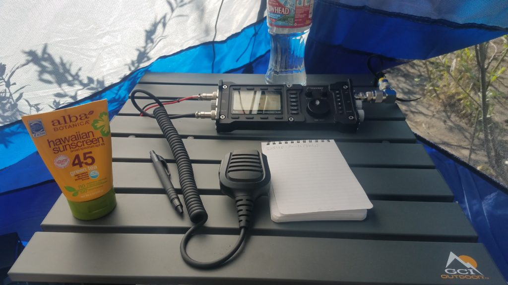 A view of the top of a metal folding table with a radio, water bottle, sunscreen, a pen, and notepad. Brush and beach sand is visible through a mesh panel.