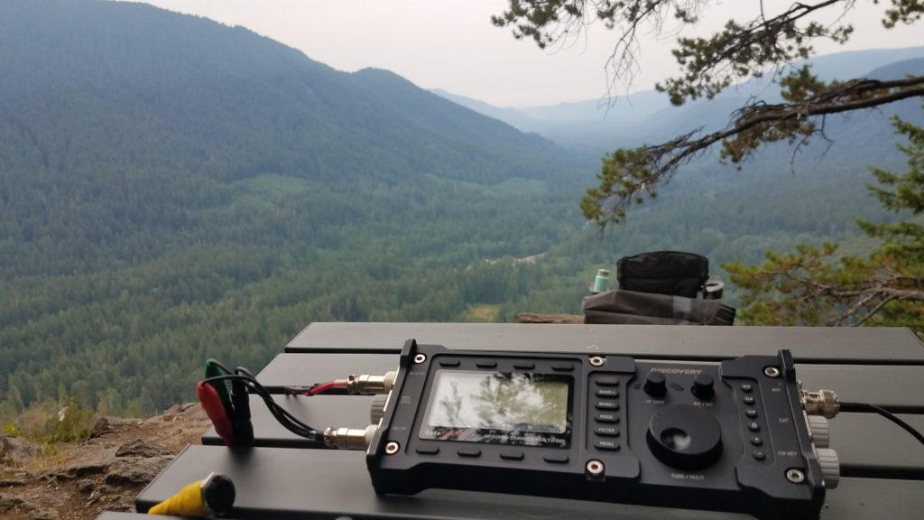 View of a heavily forested valley from a high vantage point. In the foreground a radio is sitting on a gray metal camping table.