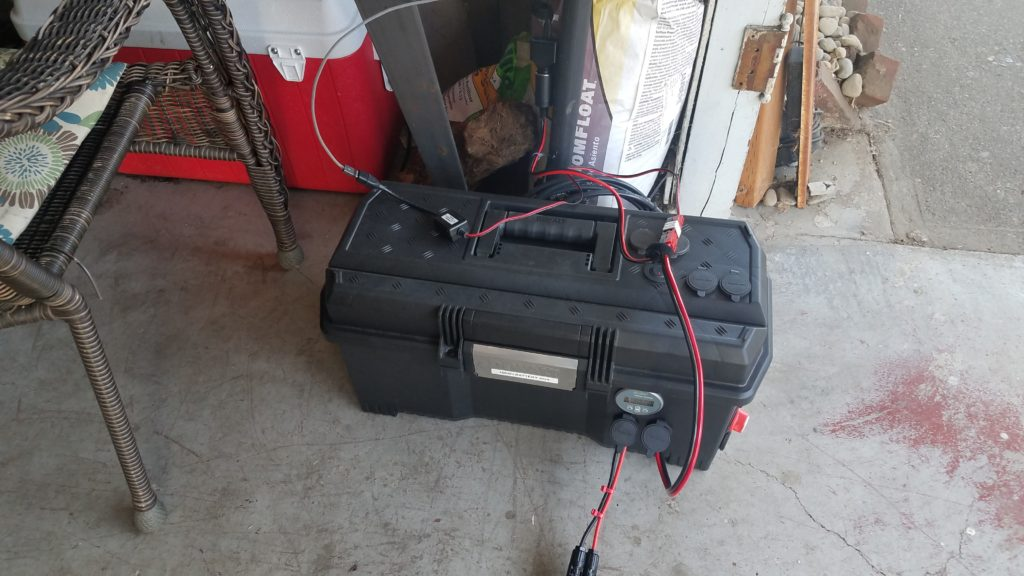 Battery box sitting on a concret slab with wires running from it.
