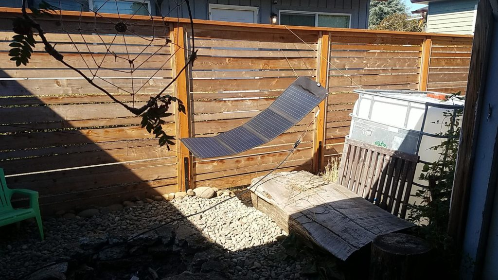 Solar panel suspended from paracord in the sun.